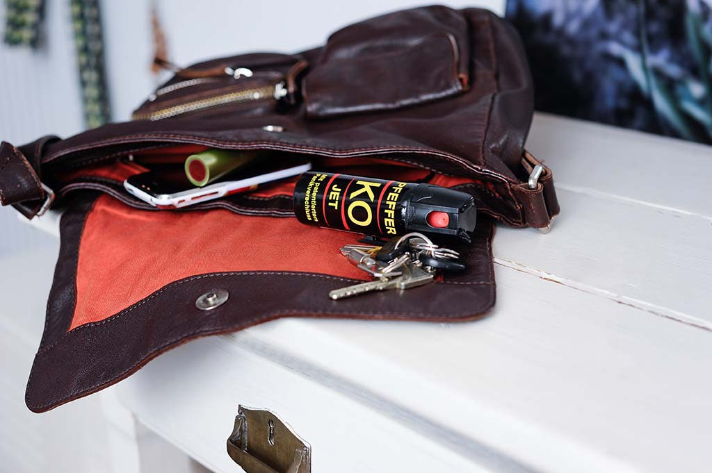 Offene Handtasche auf Kommode mit Pfefferspray darin