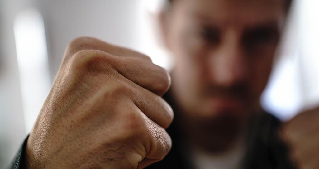 Mann mit geballter Faust, symbolisch für ein Körperverletzungsdelikt