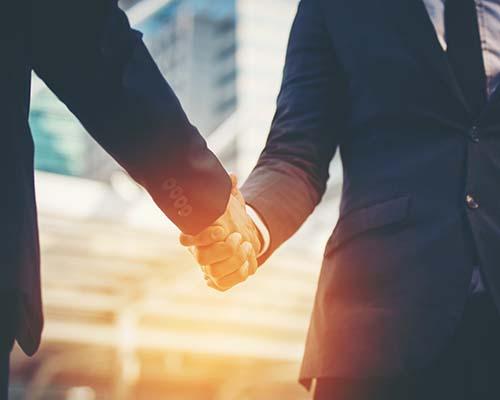 Von der Seite gesehen, zwei Anwälten, die sich die Hand geben