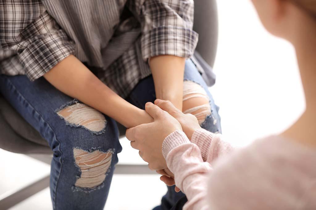 Mädchen mit blauem Fleck am Arm wird getröstet von einer Frau