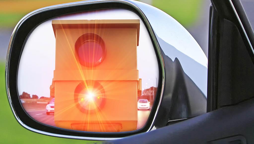 Blitzende Radarfalle im Seitenspiegels eines Autos