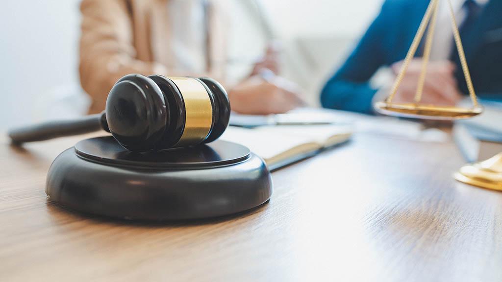 Beratungsgespräch beim Anwalt, im Vordergrund ein Richterhammer