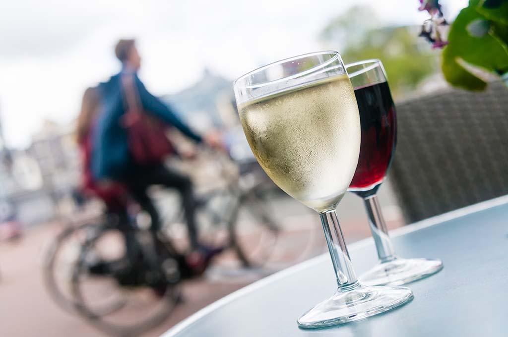 Zwei Weingläser auf einem Tisch und im HIntergrund zwei Fahrradfahrer