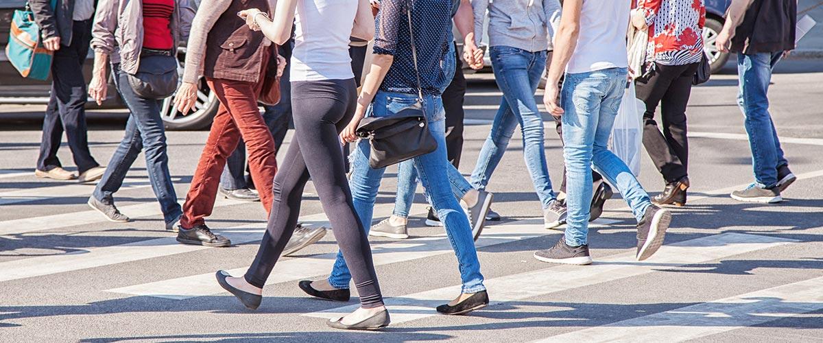 Fußgängerinnen laufen über einen Zebrastreifen als Symbol für Fußgänger im Verkehrsrecht